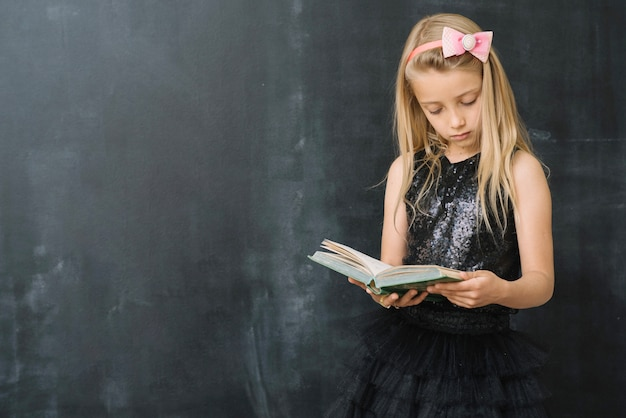 Young girl with book at chalkboard Free Photo
