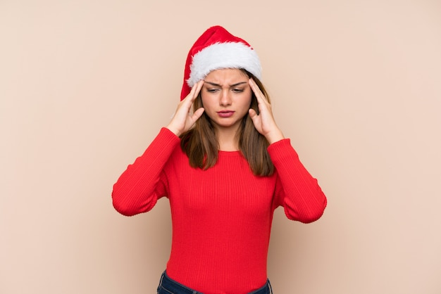 Young girl with christmas hat over isolated wall unhappy and frustrated with something. negative facial expression Premium Photo