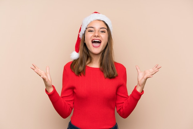 Young girl with christmas hat over isolated wall unhappy and frustrated with something Premium Photo
