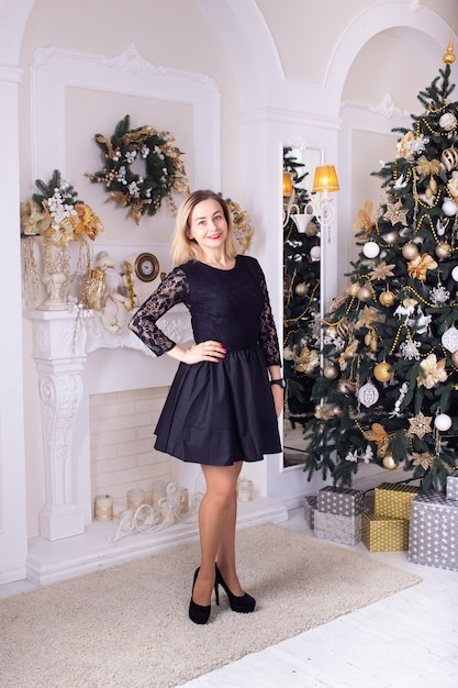 Young girl with christmas tree and fireplace Premium Photo