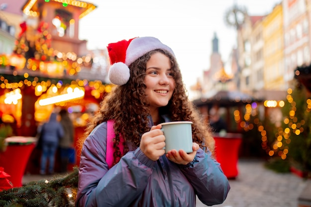 Young girl with drink on christmas market in wroclaw, poland Premium Photo