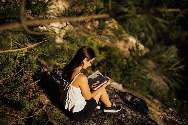 Молодая девушка в очках сидит на скале в горах и читает книгу в спокойный солнечный летний день, полный теплого света. Premium Фотографии