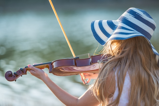 Young girl with hat playing the violin at lake. Premium Photo