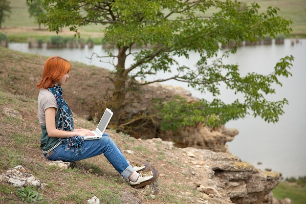 Young girl with laptop computer sitting on a bank of lake. Premium Photo