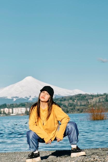 Молодая девушка с длинными черными волосами в стиле хип-хоп позирует на пирсе у озера. Premium Фотографии