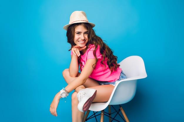 帽子の長い巻き毛を持つ少女は、スタジオで青の背景に椅子でポーズをとっています。彼女はショートパンツ、ピンクのtシャツ、白いスニーカーを着ています。彼女は膝をついたままカメラに向かって微笑む。 無料写真