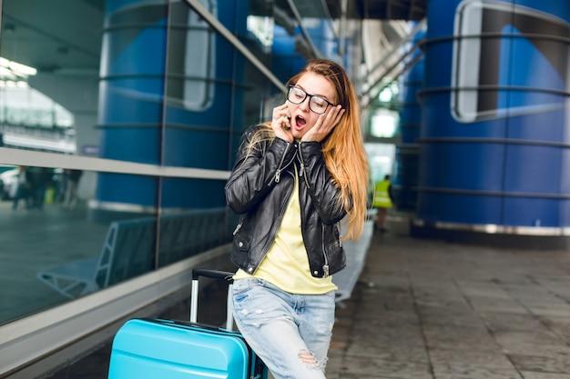 黒のジャケットで長い髪の少女は空港の外のスーツケースの近くに立っています。彼女は髪が長く、黒い眼鏡をかけています。興味をそそられる電話で話す。 無料写真
