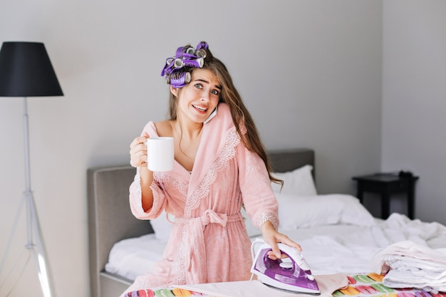 ピンクのバスローブとアイロンを押しながら自宅の電話で話す頭の上のカーラーで長い髪の少女。びっくりします。 無料写真