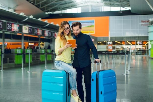 노란 스웨터에 긴 머리를 가진 어린 소녀, 청바지는 공항에서 가방에 앉아있다. 바지와 가방이 달린 검은 셔츠에 수염을 가진 남자가 근처에 서 있습니다. 그들은 태블릿에서 찾고 있습니다. 무료 사진