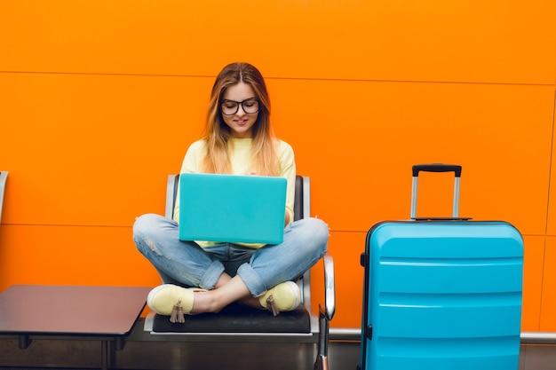 Молодая девушка с длинными волосами сидит на стуле на оранжевом фоне. на ней желтый свитер и джинсы. она печатает на ноутбуке. Бесплатные Фотографии