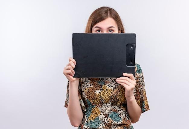 Giovane ragazza con i capelli lunghi che indossa abiti colorati che nasconde la sua faccia dietro appunti Foto Gratuite