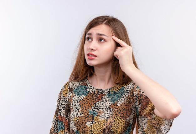 Giovane ragazza con i capelli lunghi che indossa abiti colorati che punta il suo tempio cercando di ricordare Foto Gratuite