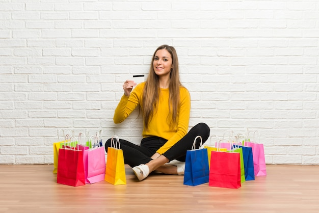 Young girl with lot of shopping bags holding a credit card Premium Photo
