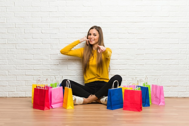 Young girl with lot of shopping bags making phone gesture and pointing front Premium Photo