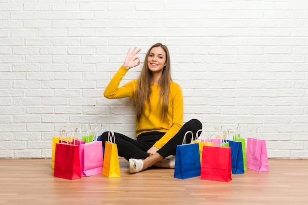 Young girl with lot of shopping bags showing an ok sign with fingers Premium Photo