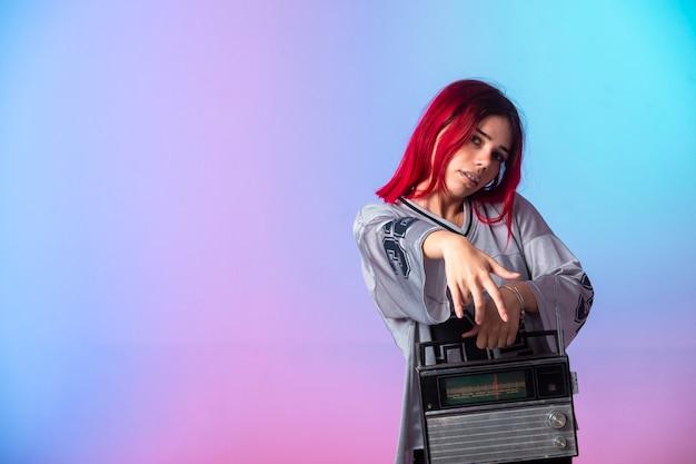 ヴィンテージラジオを保持しているピンクの髪の少女。 無料写真