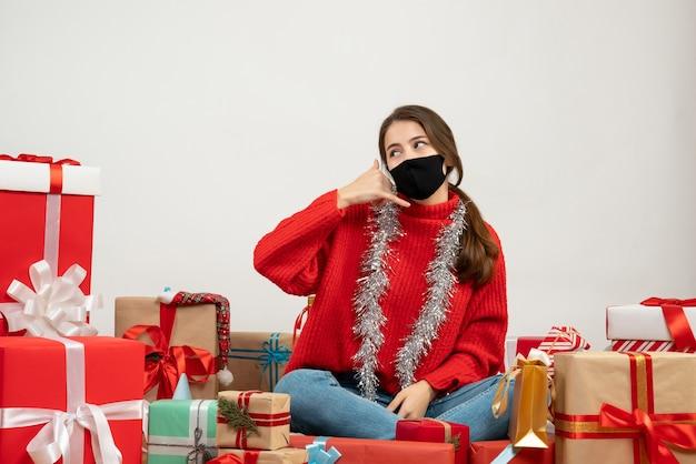 Giovane ragazza con maglione rosso e maschera nera facendo chiamarmi segno di telefono seduto intorno presenta su bianco Foto Gratuite