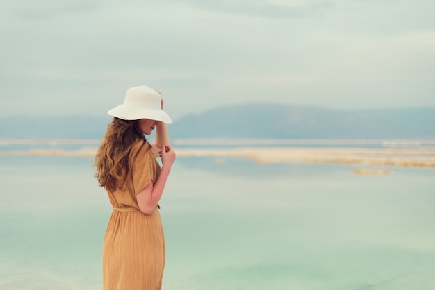Young girl with shining blonde hair goes to seaside Premium Photo