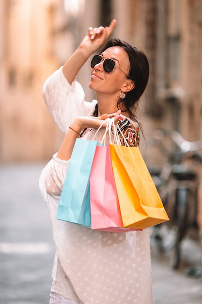 Young girl with shopping bags on narrow street in europe. Premium Photo