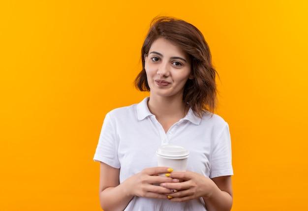 幸せそうな顔で笑顔のカメラを見てコーヒーカップを保持している白いポロシャツを着て短い髪の少女 無料写真
