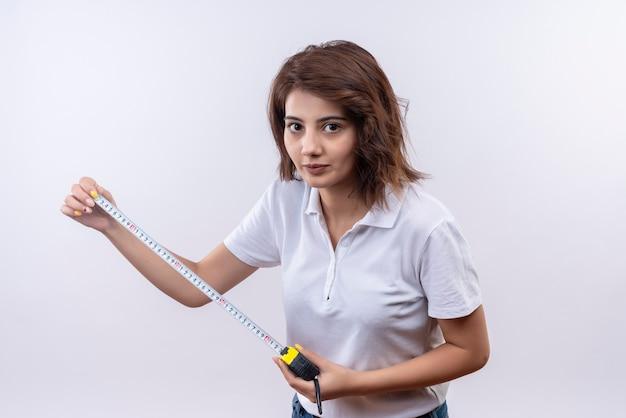 자신감이 표정으로 카메라를보고 측정 테이프를 사용하여 흰색 폴로를 입고 짧은 머리를 가진 어린 소녀 무료 사진