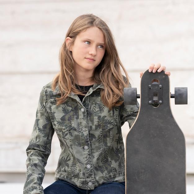 スケートボードを持つ若い女の子 Premium写真