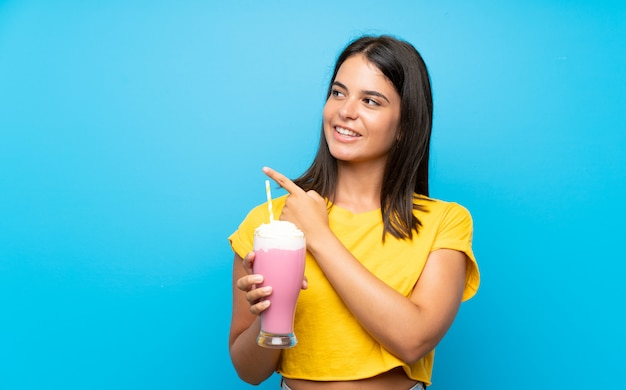 Young girl with strawberry milkshake over isolated wall pointing to the side to present a product Premium Photo