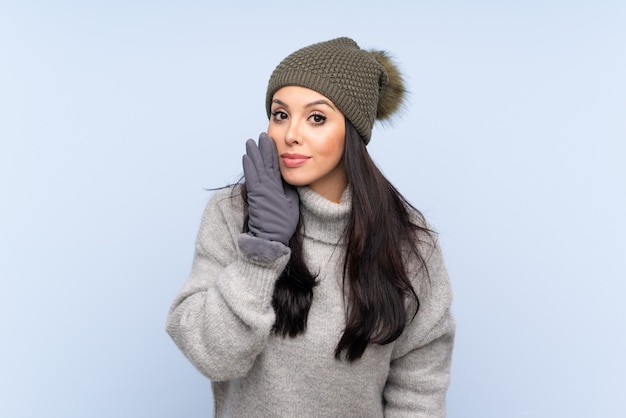 Young girl with winter hat over blue whispering something Premium Photo