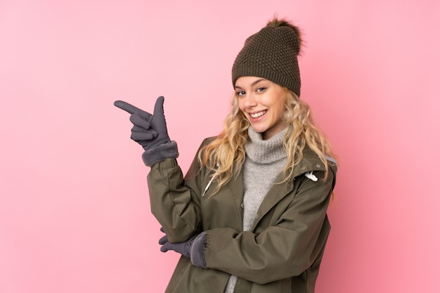 Young girl with winter hat on pink pointing finger to the side Premium Photo