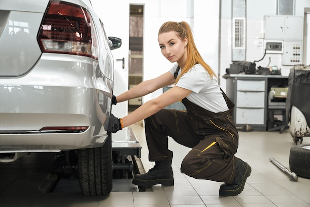 Young girl working in service station with vehicles. Free Photo