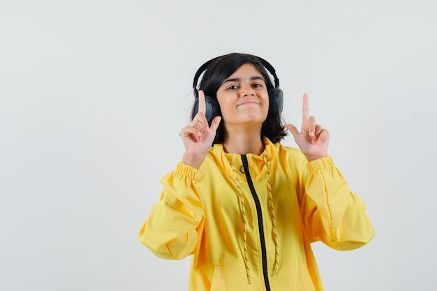 Giovane ragazza in bomber giallo ascoltando musica con le cuffie e rivolto verso l'alto con il dito indice e guardando felice Foto Gratuite