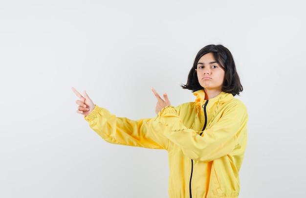 Giovane ragazza in bomber giallo e gonna rosa che punta a sinistra con il dito indice e sembra seria Foto Gratuite