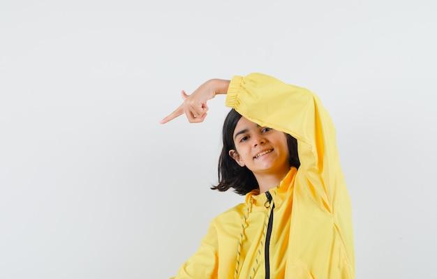 Giovane ragazza in bomber giallo e gonna rosa che punta nell'angolo inferiore sinistro con il dito indice e sembra felice Foto Gratuite