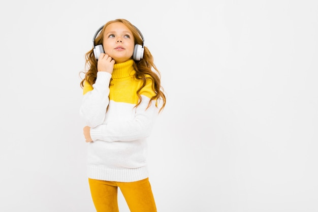 Young girl in a yellow and white sweater listens to music and looks up Premium Photo