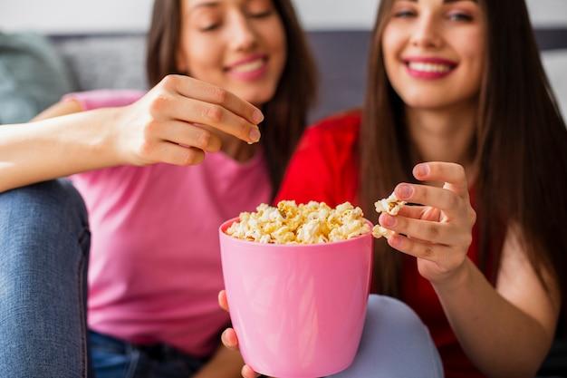 Молодые подружки дома едят попкорн Бесплатные Фотографии