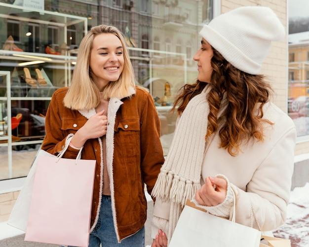 Giovani amiche all'aperto con borse della spesa Foto Gratuite