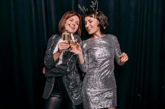 Молодые девушки вместе празднуют новый год Premium Фотографии