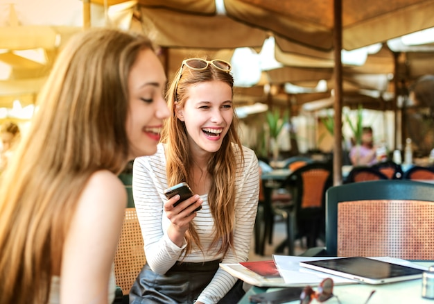 Young girls laughing on a cafe's terrace Premium Photo