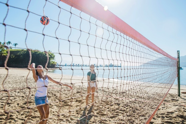 Young girls playing volley on the beach Free Photo