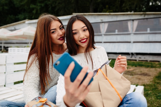 Young girls taking a photo with the mobile Free Photo