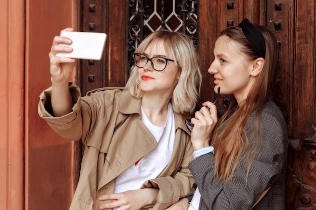 電話でselfiesを取っている若い女の子。通りの壁にあるスマートフォンのソーシャルメディアの自分撮り写真。驚きの顔、感情。 Premium写真
