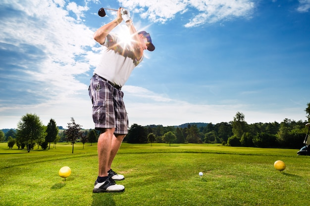 Young golf player on course doing golf swing Premium Photo