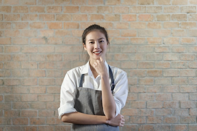 Young good looking asian barista standing in coffee shop with beautiful brick wall in background. Premium Photo