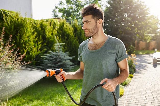 Giovane uomo caucasico barbuto di bell'aspetto con l'acconciatura alla moda in t-shirt blu concentrato irrigazione giardino con tubo flessibile. Foto Gratuite