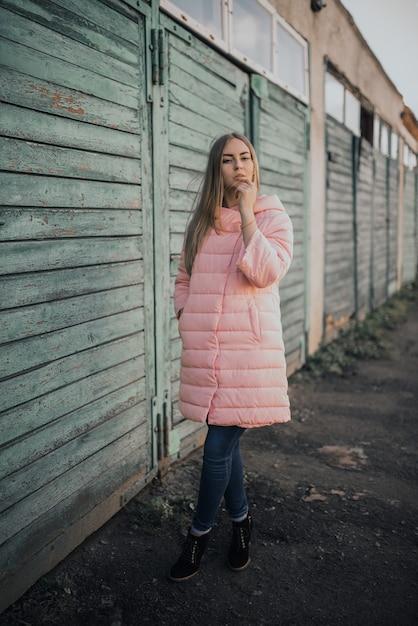 若いゴージャスなブロンドの女の子は、ファッションのピンクのジャケットとブルージーンズを着ています。 Premium写真