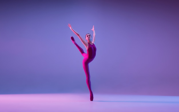 Young and graceful ballet dancer isolated on purple studio background in neon light Free Photo