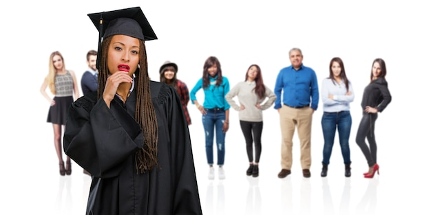 Young graduated black woman wearing braids doubting and confused Premium Photo