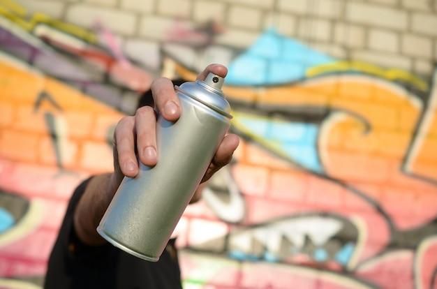 젊은 낙서 예술가 핑크 톤에 다채로운 낙서의 배경에 그의 스프레이 캔을 목표로 프리미엄 사진