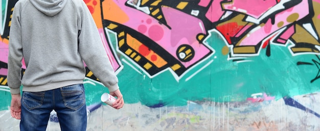 A young graffiti artist in a gray hoodie looks at the wall Premium Photo