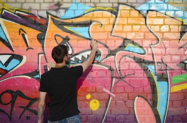 그의 목에 배낭과 가스 마스크와 젊은 낙서 예술가는 벽돌 벽에 핑크 톤의 화려한 낙서를 페인트 프리미엄 사진